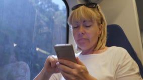 Jonge mooie vrouwentoerist die door trein reizen, zittend naast een venster, die een smartphone gebruiken Het concept reis stock footage