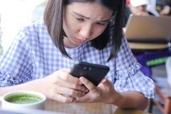 Jonge mooie vrouwenzitting bij lijst met groene thee die latte slimme mobiele telefoon met behulp van die zaken verzoeken die, on stock afbeeldingen