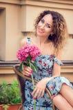 Jonge mooie vrouwenzitting in een rieten koffie van de stoelstraat Zij glimlacht gelukkig, houdend een hydrangea hortensiabloem i stock afbeelding