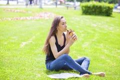 Jonge mooie vrouwenzitting in het de zomerpark Stock Foto