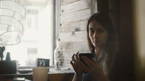 Jonge mooie vrouwenzitting in koffie dichtbij het venster en het gebruiken van smartphone, die Internet surfen terwijl het wachte stock video