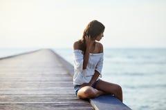 Jonge mooie vrouwenzitting op de pijler royalty-vrije stock foto
