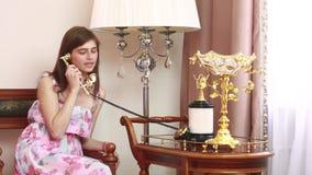 Jonge mooie vrouwenzitting op stoel, die op uitstekende telefoon spreekt, stock video