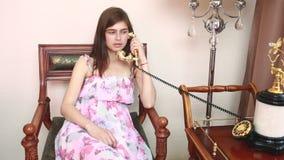 Jonge mooie vrouwenzitting op stoel, die op uitstekende telefoon spreekt, stock videobeelden