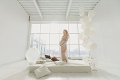 Jonge mooie zwangere vrouw die dichtbij venster zich thuis bevinden Stock Fotografie