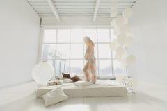 Jonge mooie zwangere vrouw die dichtbij venster zich thuis bevinden Royalty-vrije Stock Afbeelding