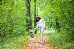 Jonge mooie zwangere vrouw die met haar babydochter lopen Stock Afbeelding
