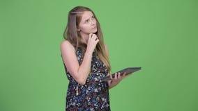 Jonge mooie zwangere vrouw die terwijl het gebruiken van digitale tablet denken stock footage