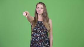 Jonge mooie zwangere vrouw die terwijl het richten van vinger denken stock video