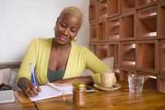 Jonge mooie zwarte Afrikaanse Amerikaanse bedrijfsvrouw die bij koffiewinkel werken die gelukkige nemende nota's in blocnote glim stock afbeelding