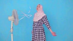 Jonge Moslimdievrouw door ventilator in heet weer wordt gekoeld stock footage