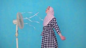 Jonge Moslimdievrouw door ventilator in heet weer wordt gekoeld stock videobeelden