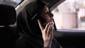 Jonge moslimonderneemster in hijabzitting in auto op passagiersachterbank en het spreken op celtelefoon, die uit kijken stock video