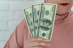 Jonge moslimvrouw in de roze greep van hijabkleren van contant geldgeld in dollarbankbiljetten a in haar handen royalty-vrije stock foto