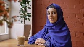 Jonge moslimvrouw die in hijab camera en glimlachen bekijken, die in moderne koffie, dame met doordrongen neus zitten stock videobeelden