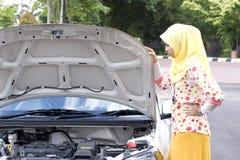 Jonge moslimvrouw die motor controleren Stock Foto's