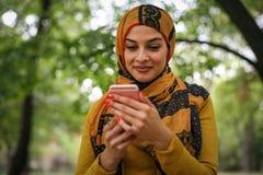 Jonge Moslimvrouw die slimme telefoon met behulp van stock afbeelding