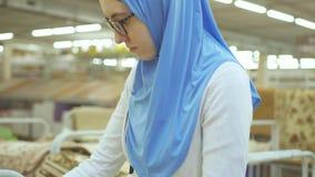 Jonge moslimvrouw in een hijab en glazen in een tapijtopslag stock videobeelden