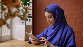 Jonge moslimvrouw in het blauwe hijab typen op tablet en het zitten in moderne koffie, charmante dame met doordrongen neus stock video