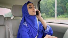 Jonge moslimvrouw in hijab in auto op passagierszetel die op telefoon spreken en aan bestuurder spreken stock videobeelden