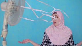 Jonge Moslimvrouw in hijab die aan heet weer lijdt dat door ventilator wordt gekoeld, die camera bekijkt stock videobeelden