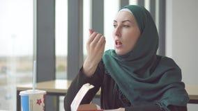 Jonge moslimvrouw in hijabzitting bij de lijst door het venster in snel voedsel en het eten van aardappels