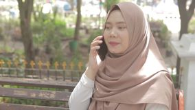 Jonge moslimvrouwenzitting op bank terwijl besprekingen met iemand op telefoon stock video