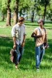 Jonge multi-etnische mensen die boeken en rugzak houden terwijl het lopen samen in park Royalty-vrije Stock Afbeelding