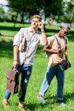 Jonge multi-etnische mensen die boeken en rugzak houden terwijl het lopen samen in park Stock Foto's