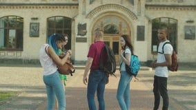 Jonge multi etnische studenten die aan universiteit lopen stock video