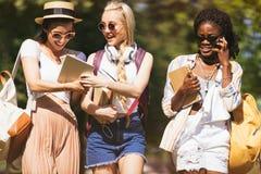 Jonge multi-etnische studenten die boeken en digitale apparaten houden terwijl het spreken en het lopen in park Royalty-vrije Stock Fotografie
