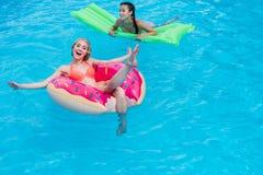 Jonge multi-etnische vrouwen die op opblaasbare matrassen in zwembad drijven royalty-vrije stock foto's