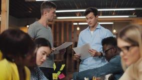 Jonge multiraciale groep mensen die in de cowerkruimte werken Zakelijke mensen werken samen, bespreken de markt tijdens vergaderi stock videobeelden
