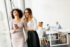 Jonge multiraciale onderneemsters die, terwijl andere businesspeo glimlachen stock foto's