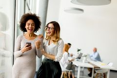 Jonge multiraciale onderneemsters die, terwijl andere businesspeo glimlachen royalty-vrije stock foto's