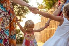 Jonge mum met de meisjes die van de blondedochter doend ring rond rosie glimlachen Warm zonsonderganglicht De reis van de familie royalty-vrije stock fotografie