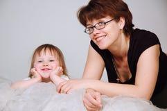 Jonge mum met een dochter ligt op een bed Stock Afbeeldingen