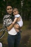 Jonge mumgangen met baby in het park Royalty-vrije Stock Fotografie