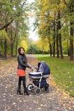 Jonge mumgangen met kinderwagen in het de herfst gele park Stock Afbeeldingen