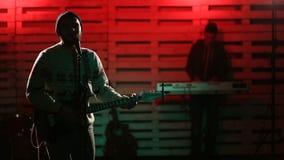 Jonge musicus die elektrische gitaar en het zingen spelen stock videobeelden