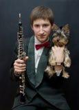 Jonge musicus met de hond van Yorkshire. Stock Foto's