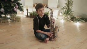 Jonge musicus, saxofonistzitting op de vloer in de ruimte van het huis op de achtergrond van Kerstmisdecoratie stock videobeelden