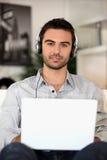 Jonge muziekminnaar met oortelefoons en laptop Royalty-vrije Stock Afbeelding
