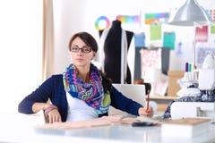 Jonge naaister die klerenpatroon op papier ontwerpen Stock Foto's