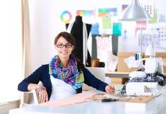 Jonge naaister die klerenpatroon op papier ontwerpen Stock Foto