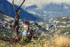Jonge naakte vrouwelijke fotograaf met professionele camera dichtbij grote oude boom tegenover Grieks dorp Een meisje met camera  Royalty-vrije Stock Fotografie