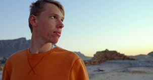 Jonge nadenkende mensenzitting op strand 4k stock video