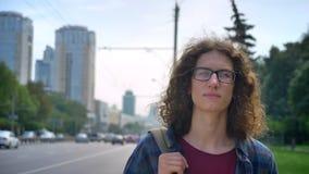 Jonge nerdy mens in glazen met lang krullend haar die op taxi of bus wachten, vooruit eruit zien en op straat zich dichtbij bevin stock videobeelden