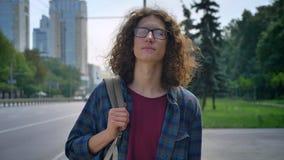 Jonge nerdy student in glazen met lang krullend op taxi wachten, zich op bushalte bevinden en stedelijk haar die, vooruit eruit z stock videobeelden