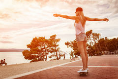 Jonge onbezorgde vrouw die een skateboard langs de kust berijden Royalty-vrije Stock Fotografie